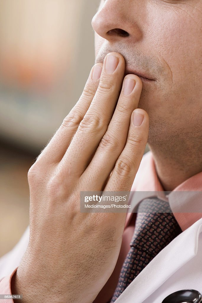 Close-up of a male doctor covering his mouth with his hand : Stock Photo