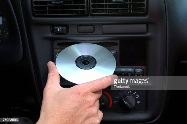 close-up of a male hand putting a cd in the car stereo. - personal compact disc player stock pictures, royalty-free photos & images