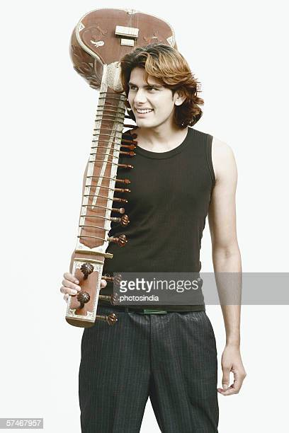 Close-up of a male musician holding a sitar