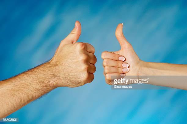 close-up of a man and a woman's hands making a thumbs up sign - dedo humano fotografías e imágenes de stock