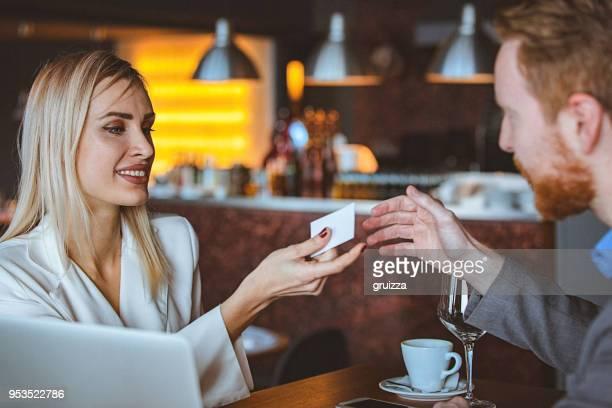 close-up of a man and woman exchanging business card in a cafe / restaurant - biglietto da visita foto e immagini stock