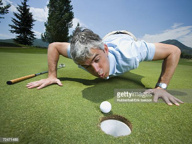 Close-up of a man blowing a golf ball towards a hole