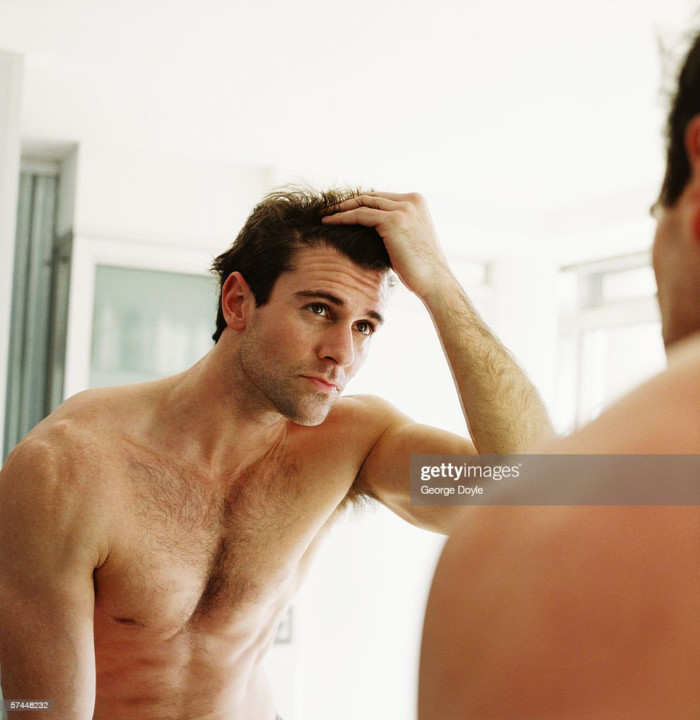 close-up of a man checking his hair in the mirror : Stock Photo