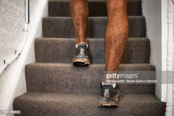 close-up of a man entering the house with his dirty shoes after training - dirty stock pictures, royalty-free photos & images