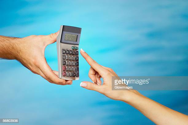 Close-up of a man holding a calculator with a woman's finger pressing a button