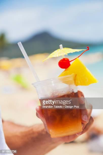 close-up of a man holding a mai tai drink with diamond head and waikiki beach in the background - mai tai fotografías e imágenes de stock