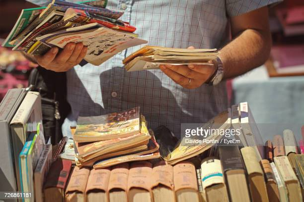 close-up of a man holding books at flea market - flea market stock pictures, royalty-free photos & images