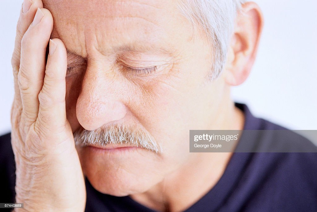 close-up of a man holding the side of his face : Stock Photo