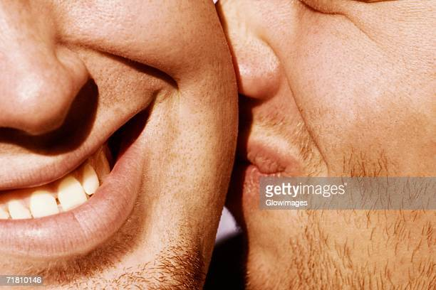 close-up of a man kissing another man - cheek stock pictures, royalty-free photos & images