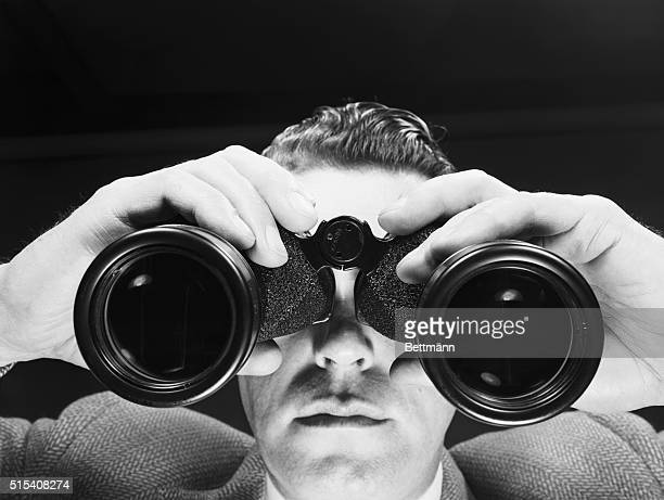 Closeup of a man looking through binoculars Undated photograph