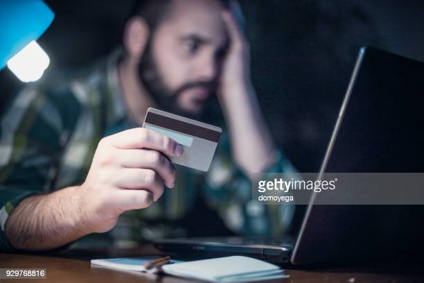 close-up of a man paying bills from home by using a laptop and a credit card - pirata informatico foto e immagini stock