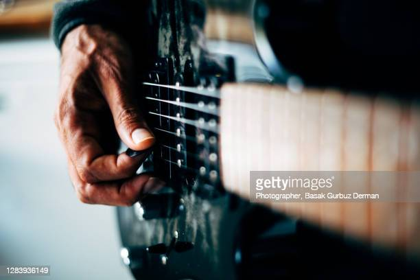 close-up of a man playing guitar - rock music stock pictures, royalty-free photos & images