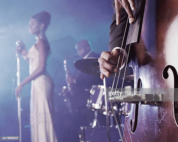 close-up of a man plucking a double bass on stage in a nightclub and a female singer and saxophonist standing in the background - jazz stock pictures, royalty-free photos & images