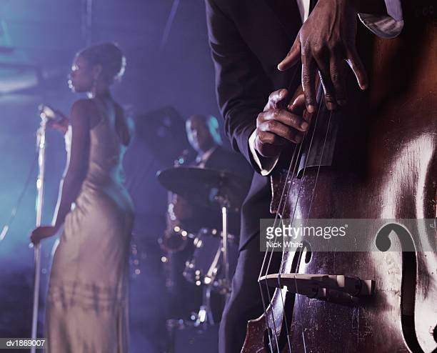 close-up of a man plucking a double bass on stage in a nightclub and a female singer and saxophonist standing in the background - club singer fotografías e imágenes de stock
