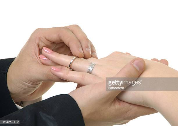 Close-up of a man putting the wedding ring on a woman's finger
