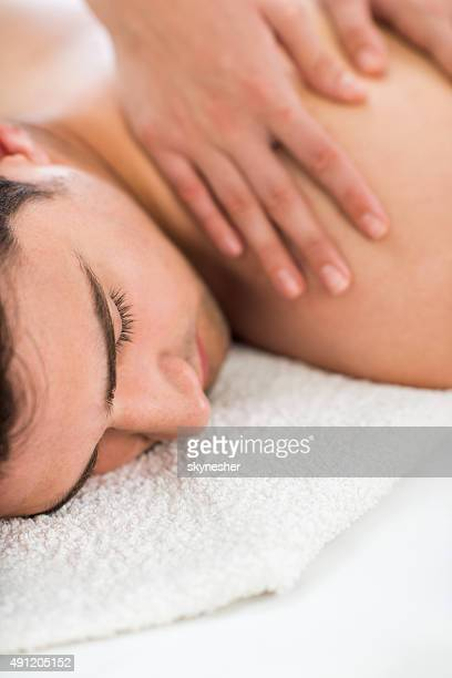 Close-up of a man receiving back massage.