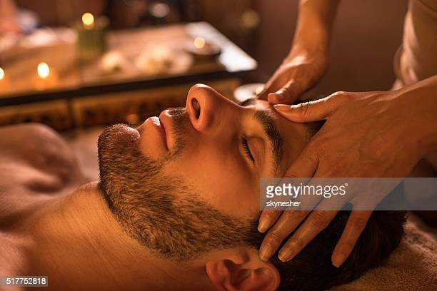 close-up of a man receiving facial massage at the spa. - massage stock photos and pictures