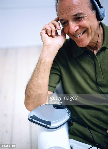 close-up of a man sitting and listening to music with headphones - personal compact disc player stock pictures, royalty-free photos & images