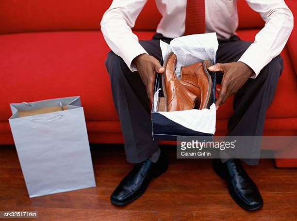 close-up of a man sitting on a couch holding a shoebox