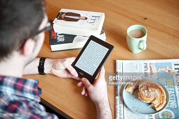 A closeup of a man using a Kindle Paperwhite ereader whilst enjoying morning coffee January 17 2013