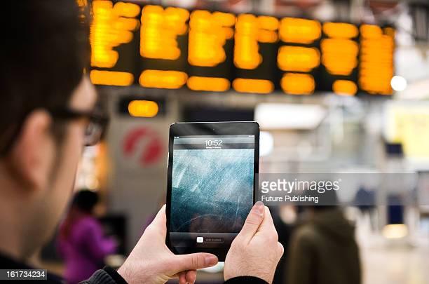 A closeup of a man using an Apple iPad Mini tablet computer at London's Paddington Station on January 14 2013