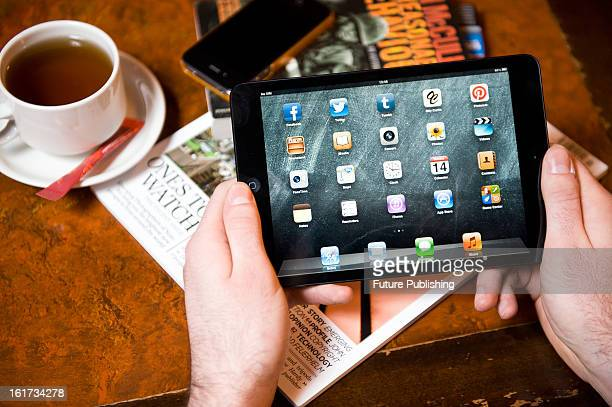 A closeup of a man using an Apple iPad Mini tablet computer in a cafe setting on January 14 2013