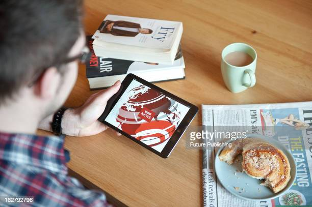 Close-up of a man using an Apple iPad Mini tablet computer to read the news, January 17, 2013.