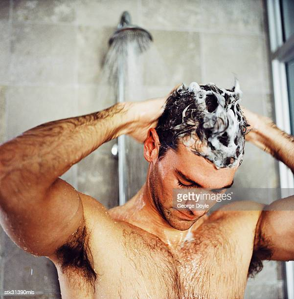 close-up of a man washing his hair in the shower - shampoo stock-fotos und bilder