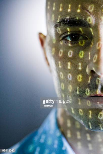 Close-up of a man with digital numbers reflected on his face.