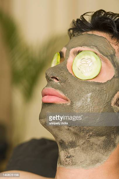 Close-up of a man with mud pack and cucumber slices on eyes