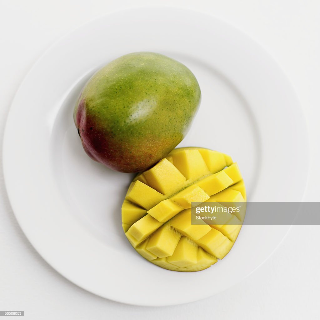 closeup of a mango and a slice of mango on a plate ストックフォト