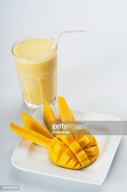 Close-up of a mango slices in a plate with a glass of mango shake
