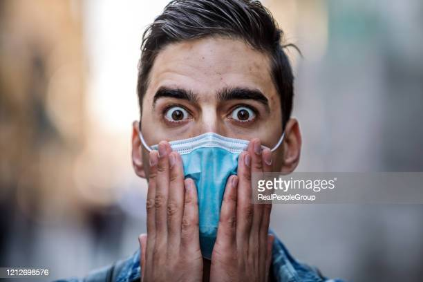 close-up of a man's face in a medical protective mask - terrified stock pictures, royalty-free photos & images