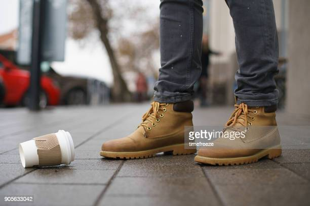Close-up of a mans feet standing in street next to a disposable cup