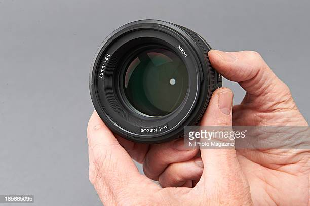 A closeup of a man's hand holding a Nikon 85mm f/18G AFS camera lens photographed during a studio shoot for NPhoto Magazine August 31 2012