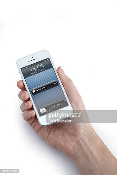 This image has been digitally manipulated A closeup of a man's hand holding a white Apple iPhone 5 smartphone taken on October 24 2012