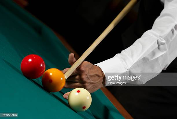 Close-up of a man's hand playing snooker