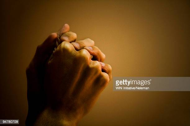 close-up of a man's hand praying - praying stock pictures, royalty-free photos & images