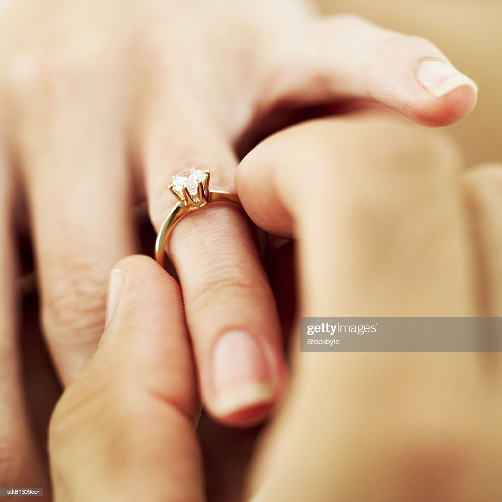 close-up of a man's hand putting a diamond engagement ring a woman's finger : Stock Photo