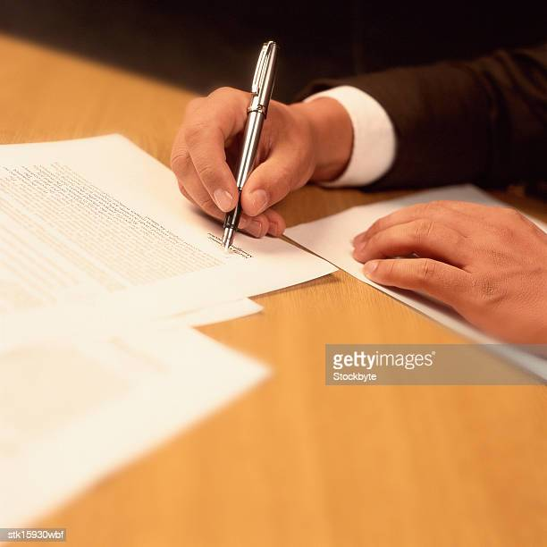 close-up of a mans hand signing on a document