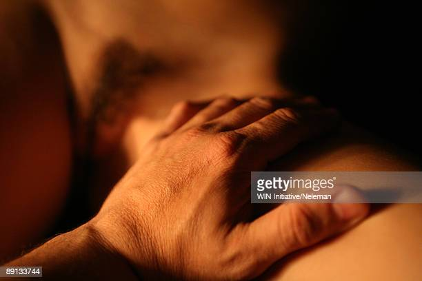 Close-up of a man's hand touching woman's thigh