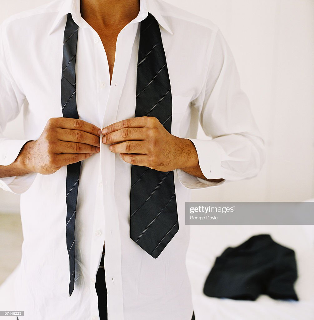close-up of a man's hands buttoning a shirt : Stock Photo