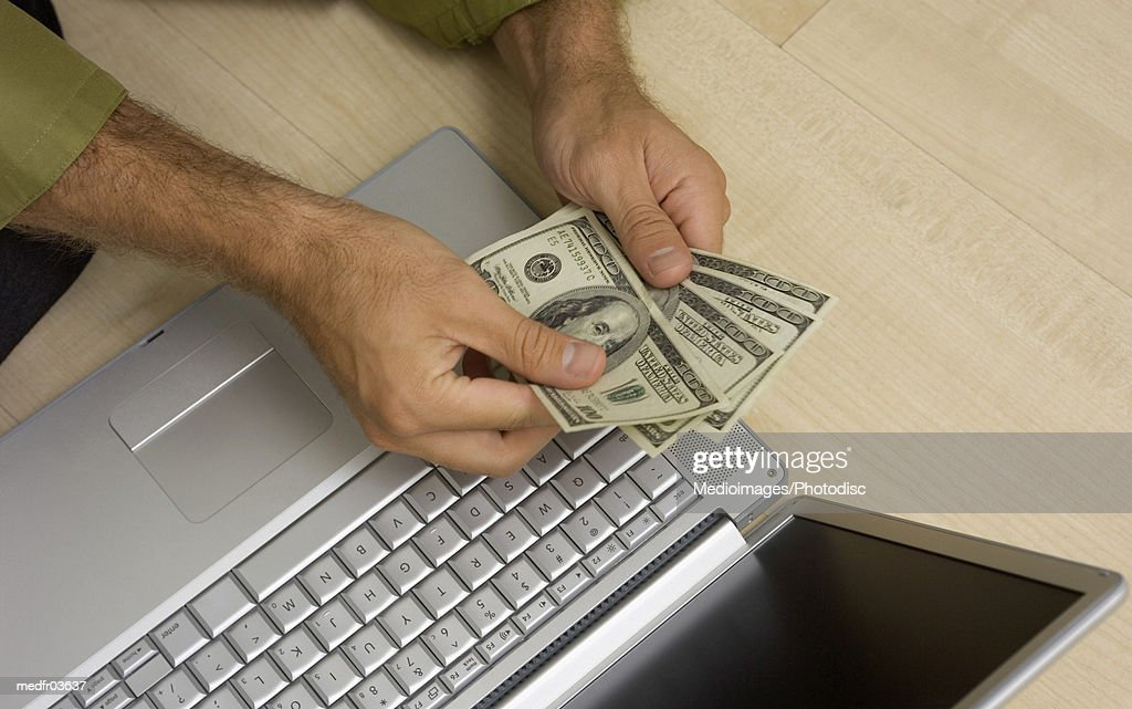 Close-up of a mans hands counting cash over a laptop : Stock Photo