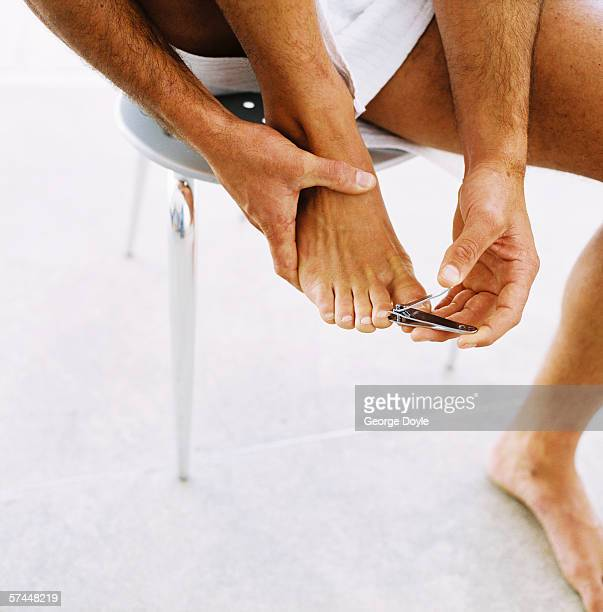 close-up of a man's hands cutting his toenails with a nail cutter