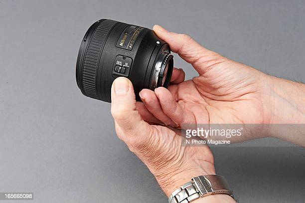 A closeup of a man's hands holding a Nikon 85mm f/18G AFS camera lens photographed during a studio shoot for NPhoto Magazine August 31 2012