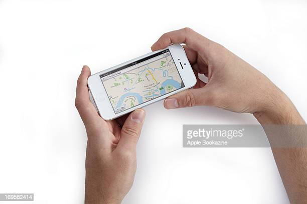 This image has been digitally manipulated A closeup of a man's hands using a white Apple iPhone 5 smartphone to view maps taken on October 24 2012