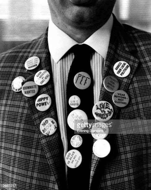 A closeup of a man's jacket adorned with badges making diverse statements such as 'Hippy Power' 'I Like Orgies' and 'No More War'