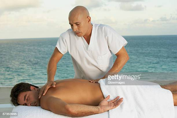 Close-up of a massage therapist giving a young man a back massage