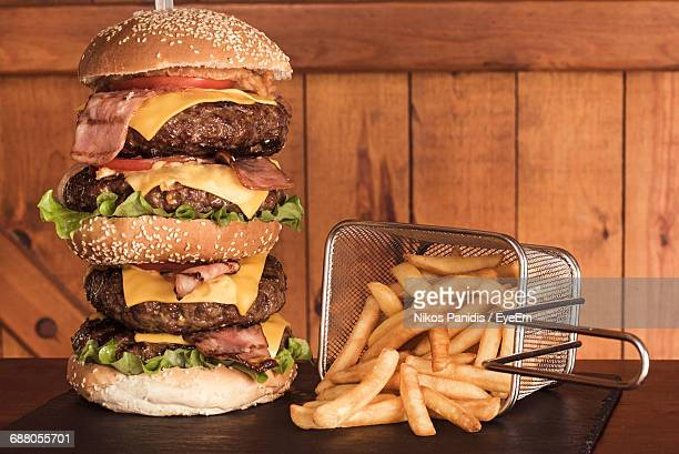 close-up of a massive, tripple stack hambuger and fries  - cheeseburger stock pictures, royalty-free photos & images