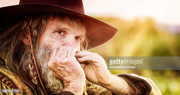 close-up of a mature cowboy playing the harmonica - soul music stock pictures, royalty-free photos & images